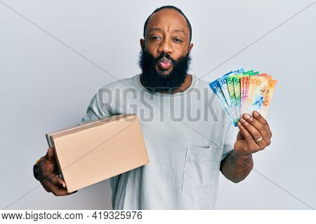 Young african american man holding delivery box and swiss franc banknotes looking at the camera blowing a kiss being lovely and sexy. love expression.