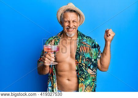 Middle age grey-haired man wearing summer style drinking cocktail screaming proud, celebrating victory and success very excited with raised arm