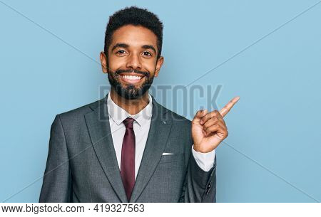 Young african american man wearing business clothes with a big smile on face, pointing with hand and finger to the side looking at the camera.