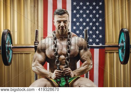 Old Fashion Bodybuilder Doing Exercises In Old School Gym With American Flag. Handsome Caucasian Spo
