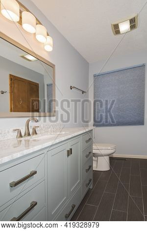 Remodeled Bathroom Interior Facing Vanity With Marble Countertop Sink Mirror Fixture And Toilet