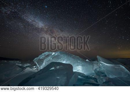Night Stars Milky Way Time Lapse At Lit Big Blue Ice Blocks. Baikal Lake In Winter Time.