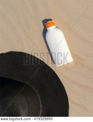 Sunscreen Lotion Next To A Black Hat On The Sand On A Sunny Day At The Beach. Kin Protection Cosmeti