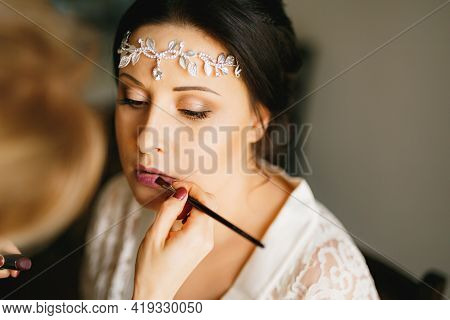 Makeup Artist Makes Makeup To The Bride In A Hotel Room During Preparation For The Wedding Ceremony,