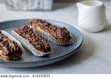 Three Eclairs On Blue Plate And Creamer On Grey Background