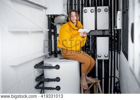 Confused Woman Looks At Electricity Bills, Comparing Data With The Meter In The Electrical Panel At