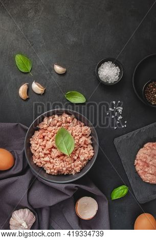 Raw Minced Meat In Bowl On Black Table And Ingredients. Ground Meat With Ingredients For Cooking On