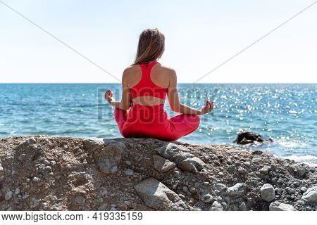 A Young Woman In Red Leggings And A Red Top With Long Loose Hair Practices Yoga Outdoors By The Sea