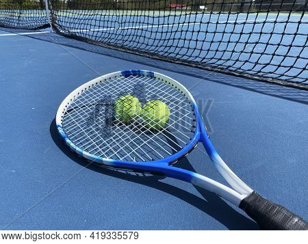 A Tennis Racket On The Ground With Two Ball Under The Racket On A Blue Court In Front Of The Net