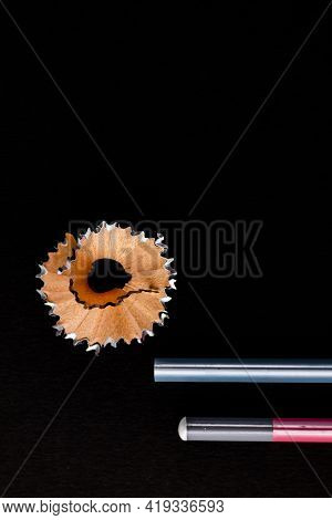 Top Close Up Shot Of Two Pencils With One Floral Shaving Waste On Black Background And Copy Space On