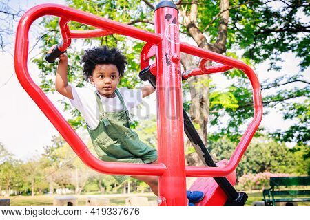 Cute African American Little Kid Boy Funny While Playing On The Exercise Machine In The Daytime In T