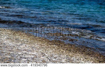 Dry Crystal Salt On Rocky Beach. Blue Sea Background.
