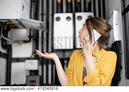 Confused Woman Having Problems With Heating System At Home, Speaks On The Phone Trying To Solve The