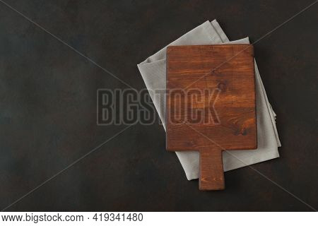 Wood Cutting Board Over Towel On Stone Kitchen Table. Top View. Food Background Cutting Board Wood T