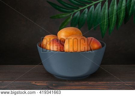 Bowl Of Raw Apricots On A Rustic Wooden Table Over Brown Background. Top View
