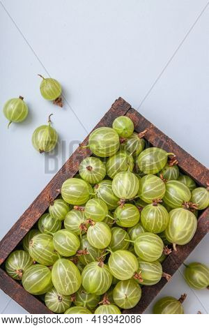 Ripe Green Gooseberry Berry In Wooden Box. Green Gooseberry On Light Blue Background. Top View