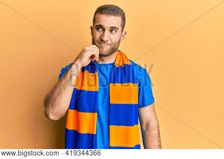 Young caucasian man football hooligan cheering game thinking concentrated about doubt with finger on chin and looking up wondering