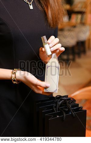 Elegant Sensual Young Woman Holding Perfume, Golden Tones