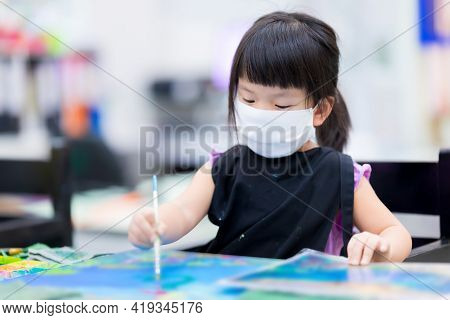 Cute Girl Is Coloring On Canvas. Kid Wear White Mask And Black Aprons Uniform While Sitting On Woode