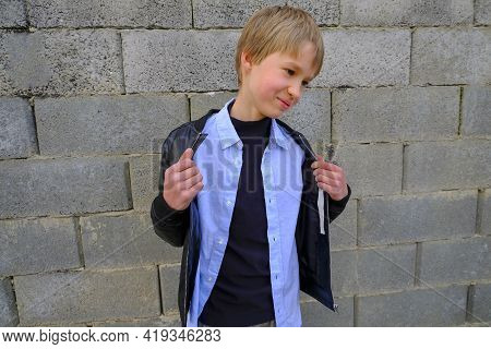 Cute Shy Blond Boy In Stylish Shirt And Black Leather Jacket Across The Gray Brick Wall. Copy Space