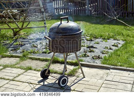 Barbeque Grill In The Blurred Spring Garden Background. Selective Focus On Barbeque Grill.