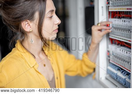 Confused Woman Having Problems With Electricity At Home, Speaks On The Phone Trying To Solve The Pro