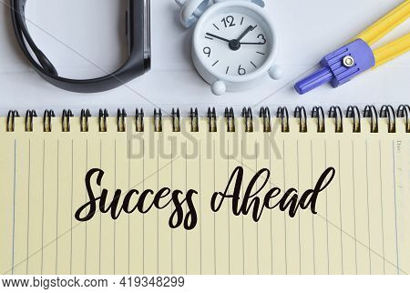 Phrase Success Ahead Written On Notebook With Clock, Watch And Math Compass