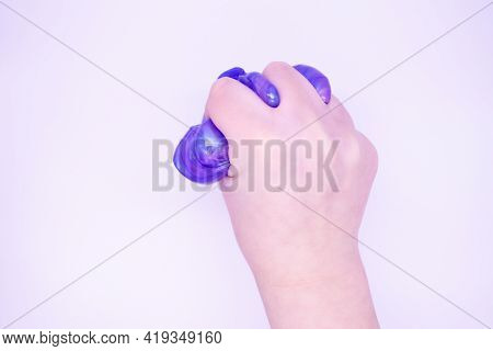 Close Up Of Game With Two-color Blue And Pink Slime In Someones Hands On A White Background. The Muc