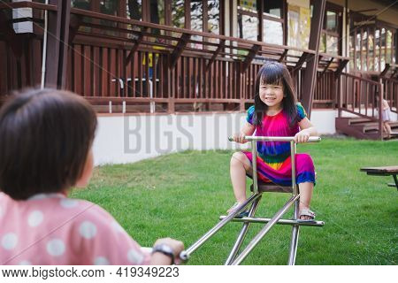 Sibling Girl Were Having Fun Playing Seesaw In The Green Lawn. Happy Kid Sweet Smiles. Children 4-5