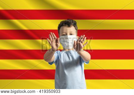 Little White Boy In A Protective Mask On The Background Of The Flag Of Catalonia. Makes A Stop Sign