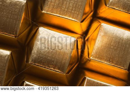 A Pattern Of Square-shaped Chocolates In A Golden Wrapper. Beautiful Food.