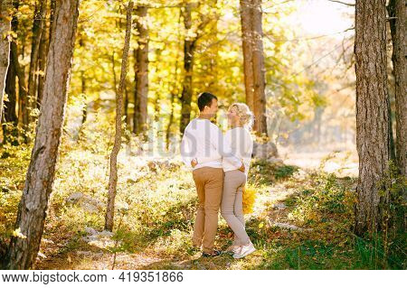 Man And Woman Are Embracing In The Autumn Forest. Back View