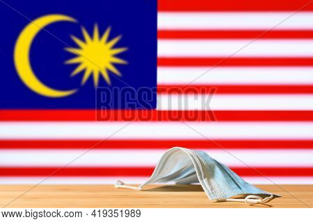 A Medical Mask Lies On The Table Against The Background Of The Flag Of Malaysia. The Concept Of A Ma