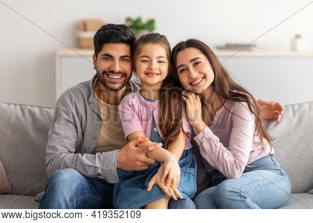 Family Portrait. Excited Arabic Parents And Cute Little Daughter Posing Together, Embracing And Smil