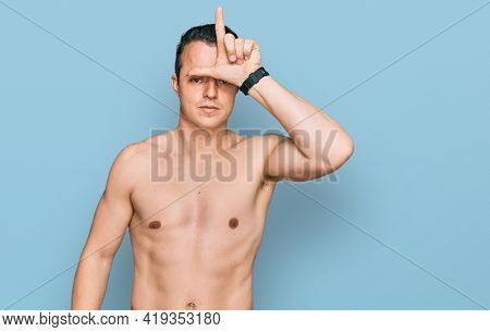 Handsome young man wearing swimwear shirtless making fun of people with fingers on forehead doing loser gesture mocking and insulting.