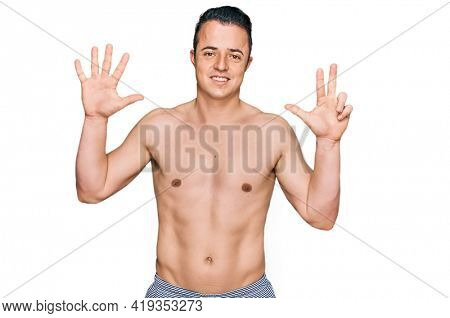 Handsome young man wearing swimwear shirtless showing and pointing up with fingers number eight while smiling confident and happy.