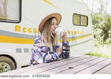 Beautiful Millennial Caucasian Woman Posing Near Camper Van In Forest. Young Stylish Woman In Shirt