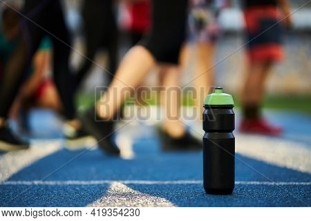 Close Up Black Sports Bottle With Green Cap Stands On A Blue Rubber Treadmill With A White Line. Wat