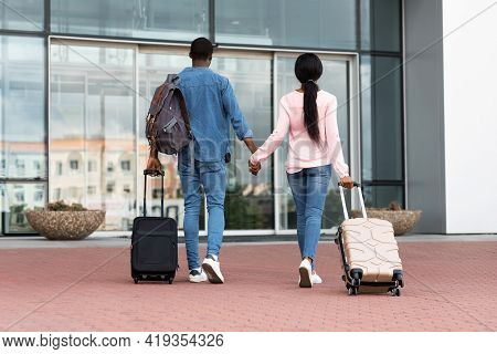 Ready For Travel. Rear View Of Black Couple With Luggage Entering Airport