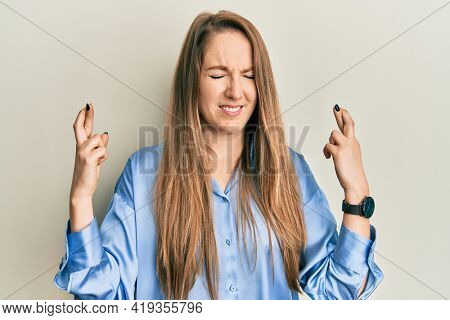 Young blonde woman wearing casual blue shirt gesturing finger crossed smiling with hope and eyes closed. luck and superstitious concept.