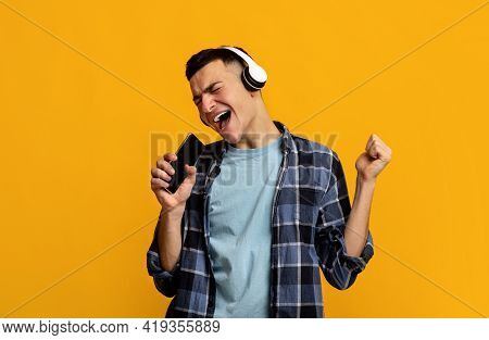 Emotional Young Man In Headphones Listening To Music, Singing Song, Using Smartphone As Mic On Orang