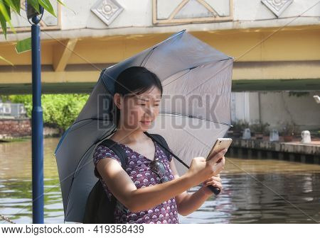 A Chinese Woman Standing Near A Bridge And Water Canal Taking A Selfie In The City Of Melaka Malaysi
