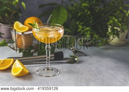 Champagne Coupe Glass Of Refreshing Orange Cocktail With Ice Served On Gray Table Surface Surround O