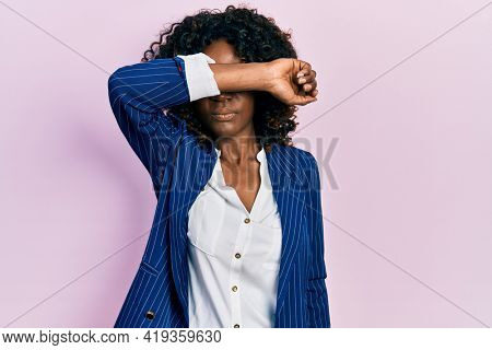 Young african american woman wearing business clothes and glasses covering eyes with arm, looking serious and sad. sightless, hiding and rejection concept