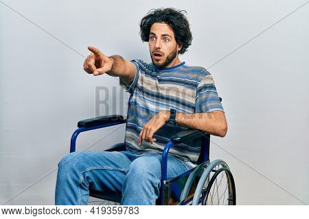 Handsome hispanic man sitting on wheelchair pointing with finger surprised ahead, open mouth amazed expression, something on the front