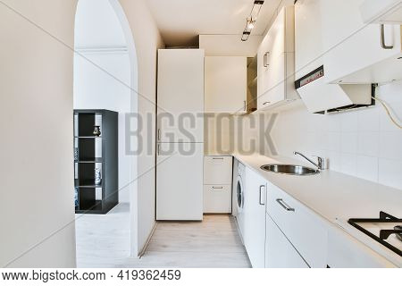 Narrow Room Of Kitchen With White Cabinets And Simple Appliance With Arched Passage To Living Room O