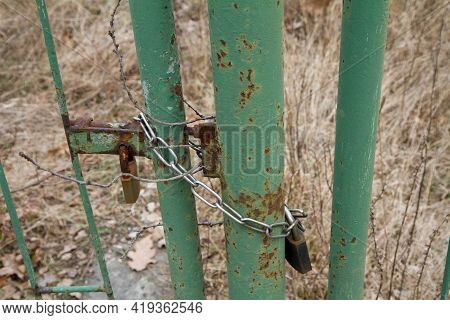 A Gate Closed With A Padlock - Focus On The Padlock