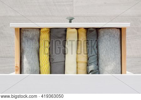 Womens Clothing In Gray And Yellow Colors Is Neatly Folded Vertically In An Open Dresser Drawer, Top
