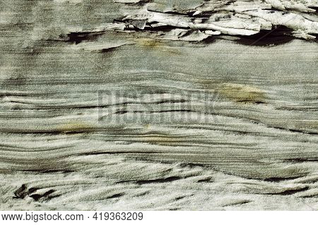 Wavy Structure Of Gray Stone With Pronounced Shadows In The Sunlight