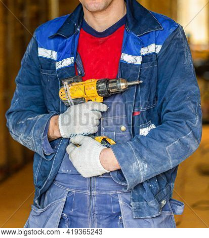 Worker In Dirty Uniform And Protective Gloves With Drill In His Hands